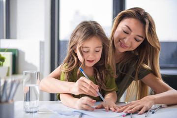 Wait up portrait of joyful mother and daughter drawing image together. They are sitting at home and laughing