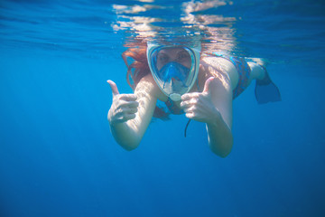 Woman snorkeling showing thumbs. Snorkel in full face mask. Female swim with loose red hair.