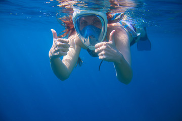 Girl underwater showing thumbs. Snorkeling woman in full face mask.
