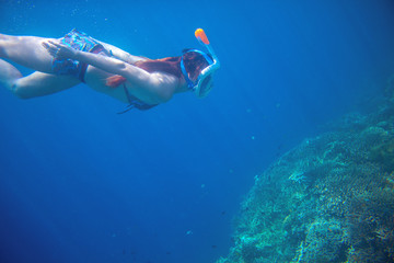 Diving girl underwater with coral reef. Snorkel in full face mask.