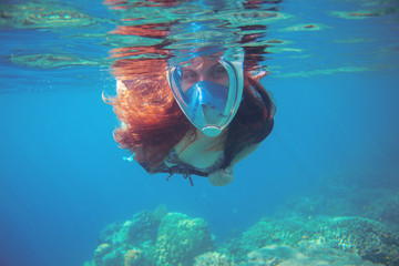 Woman swimming in blue sea. Snorkeling woman in full face mask.