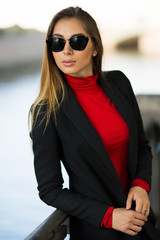 A portrait of young beautiful woman with brown long hear, in black coat, red top and sunglasses, locking aside. River on background is blurry