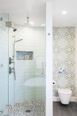 Modern glass shower with mosaic flooring, glass tiles and wallpaper above toilet.