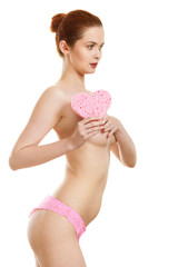 Skincare hygiene medicine and body treatment. Sensual naked woman with beautiful figure perfect skin holding pink heart shaped bath sponge in hands. Isolated on white