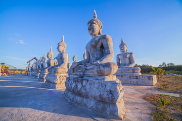 a lot of Buddha statues have many sizes are arranged in a row in the large yard of the place of religious activities.