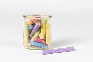 Colorful pieces of chalk in old jar on white background