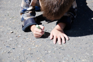 Kid drawing on asphalt in spring, child paint crayons in the park