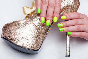 Woman with green and yellow manicured nails holding a gold high heel.