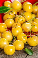 Yellow cherry in bowl on a wooden background