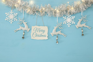 Christmas background with tree festive garland, white deer, and paper white snowflakes over light blue background.