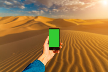 Photographing with smartphone in hand. Travel concept. Sunset in the desert
