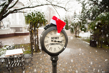 vintage street clock with text Merry Christmas and Santa Claus hat on them during snowfall