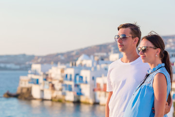 Beautiful young couple at Mykonos island, Cyclades. Tourists enjoy their greek vacation in Greece background famous Mykonos view