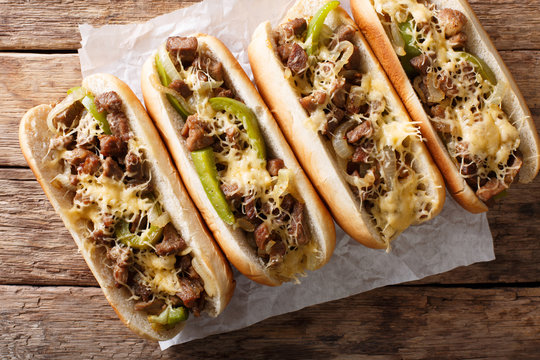 Philly cheese steak sandwich served on parchment paper close-up. horizontal top view