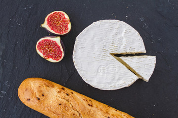 Juicy ripe pieces of fig fruit and creamy Swiss camembert cheese and a crispy golden fresh onion baguette for breakfast on a black graphite background.