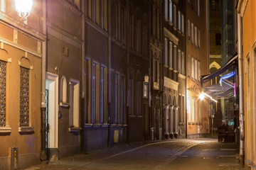View of the lit Kaletnicza Street and St. Mary's Church at the Main Town (Old Town) in Gdansk, Poland, in the evening.