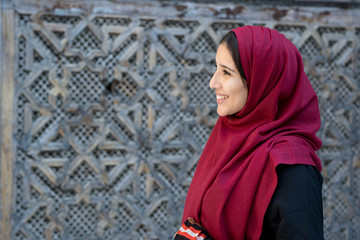 Portrait of young Arab woman in traditional clothing with red hijab in traditional ambient