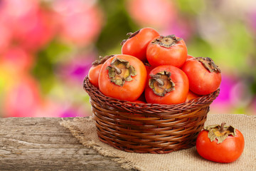 Persimmon fruit in a wicker basket on a wooden table with blurred garden background
