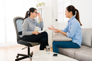 woman sitting on sofa talking with her doctor