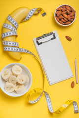 Bananas and almonds with measuring tape on yellow background with copy space