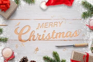 Christmas carving in white wooden board. Merry Christmas greeting text surrounded with decorations.