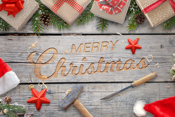 Christmas hand craft on wooden surface with hammer and chisel. Wooden carving greeting text surrounded with gifts and Christmas tree branches. Santa hat and suit beside.