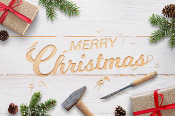 Flat Christmas greeting with carved text into white wooden surface with chisel and hammer. Christmas fir branches, gifts and pinecones beside.