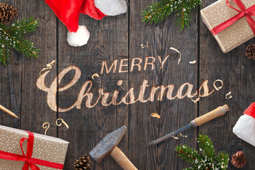 Santa Claus hand carved Merry Christmas text on wooden surface with chisel and hammer. Fir branches, presents and santa clothes beside.