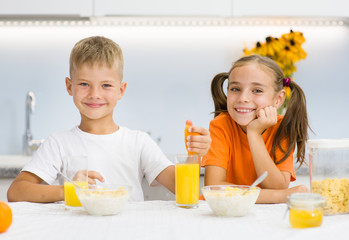 Girl and boy clink glasses with orange juice at breakfast