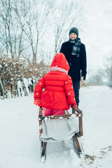 Dad rolls his child on sledge in winter