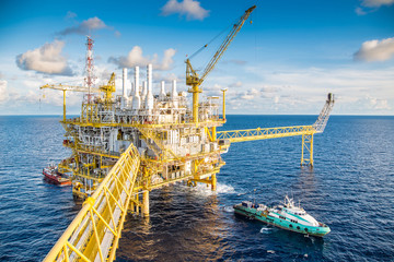 Offshore oil and gas business, boat loading cargo at offshore central processing platform.