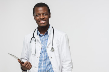 Horizontal photo of african doctor isolated on grey background smiling happily and holding his tablet computer. Concept of contemporary gadgets and medical services