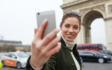 young woman visiting Paris. Triumphal arch. make selfie