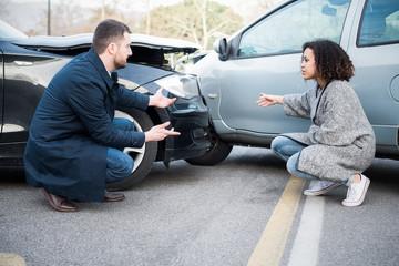 Man and woman arguing about damage after bad car crash