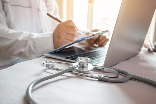 Medicine doctor's writing on laptop in medical office.Focus stethoscope on foreground table in hostpital.Stethoscope is acoustic medical device for auscultation,listening internal sounds of human body