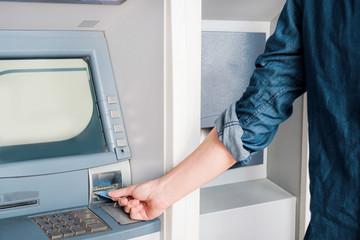 Man hand inserting credit card in an atm