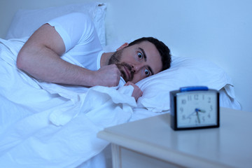 Stressed man trying to sleep in his bed