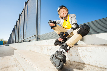 Smiling boy in roller blades sitting on the stairs