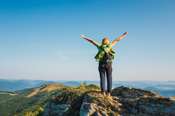 woman stands on the cliff and looks at the tops of mountains