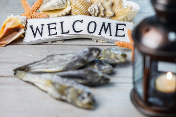Marine theme. Wooden board. Dry fish goby. Shells. A burning candle in a sea lamp. Ropes. Signboard welcome.