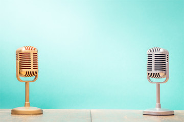 Golden and silver retro microphones on table front gradient mint green background. Vintage old style filtered photo