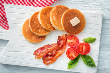 Board with yummy pancakes, tomatoes and fried bacon on wooden table