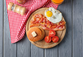 Board with yummy pancakes, tomatoes, fried bacon and egg on wooden table