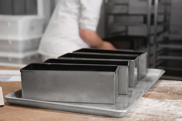 Metal forms for bread on table in bakery