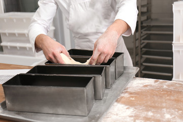Man putting dough into metal form on table in bakery