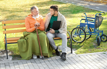 Young caregiver sitting with senior man on bench in park