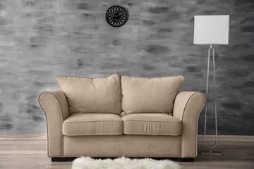 Stylish sofa with lamp near wall indoors