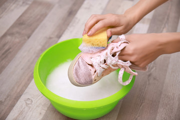 Woman washing sneaker with sponge over plastic basin, closeup