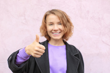 Beautiful smiling woman showing thumb up gesture near color wall