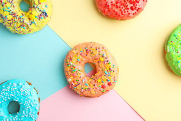 Tasty donuts with sprinkles on color background